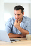 Mature man thinking using latop Stock Photo