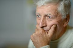 Mature man. Mature thoughtful man outdoors over gray background Stock Image
