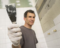 Mature Man Tiling the Bathroom with Trowel. Man tiling the bathroom. Focused close up of hand holding putty knife or trowel. Man and background are out-of-focus Stock Photos