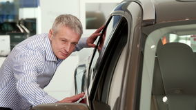 Mature man touches the car door at the dealeship stock video