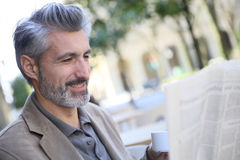 Mature man in town drinking coffee and reading newspaper Stock Photography