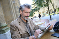 Mature man in town using tablet Royalty Free Stock Images