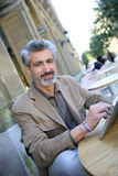 Mature man in town using tablet Stock Photography