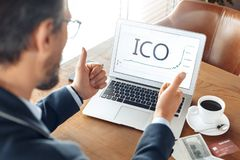 Business Lifestyle. Trader sitting at cafe with coffee and laptop using ico looking at chart thumbs up back view close stock photos