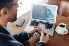 Business Lifestyle. Trader sitting at cafe with coffee looking at laptop with charts counting banknotes back view close stock images