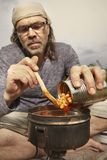 Man on trip relaxing and cooking in nature royalty free stock photography