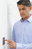 Mature Man Turning Off Light Switch At Home. Man Turning Off Light Switch stock photography
