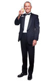 Mature man in tuxedo drinking champagne. A mature male wearing a black tuxedo and bow tie raising a glass of champagne, isolated on a white background Stock Photos