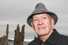 Mature Man in Tweed Rain Hat. A close up portrait of a serious elderly white man in a grey wool tweed travel roll-up rain hat standing on the beach with a moody Stock Photo