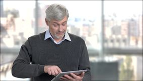 Mature man typing message on digital tablet. Friendly senior man using pc tablet on office window background. Senior people and modern technology stock footage