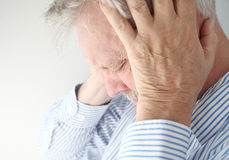 Mature man under pressure. Stressed older man holds his head in both hands Stock Photo