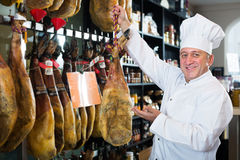 Mature man in uniform holding  tasty Spanish jamon. In local delicatessen store Stock Photography