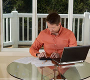 Mature man using calculator while at the home office. Photo of mature man using calculator, while working at home with laptop, and papers on top of table and royalty free stock photos