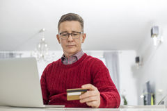 Mature man using credit card and laptop to shop online at home Royalty Free Stock Images