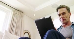 Mature man using digital tablet at home