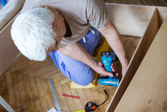 Mature man using electric screwdriver while making bookcase or s Stock Image