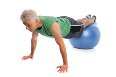 Mature Man Using Fitness Ball. Isolated over white background stock photo