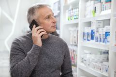 Mature man buying medications at the drugstore royalty free stock photo