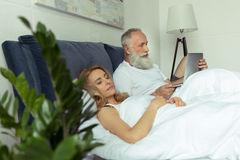 Mature man using laptop in bed while blonde woman sleeping Royalty Free Stock Images