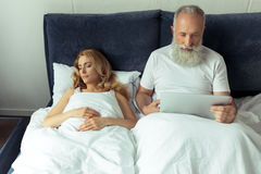Mature man using laptop in bed while blonde woman sleeping royalty free stock photo