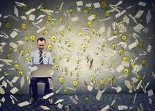 Mature man using a laptop building online business dollar bills and light bulbs falling down. stock photos