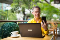 Mature Man Using Laptop Computer And Mobile Phone stock photos