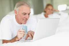 Mature man using laptop and credit card on bed Royalty Free Stock Photography