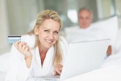 Mature man using laptop and credit card on bed Stock Photography