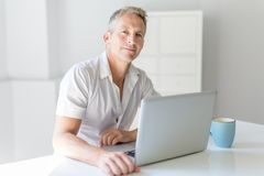 Mature Man Using Laptop On Desk At Home. A mature Man Using Laptop On Desk At Home Stock Photos