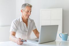 Mature Man Using Laptop On Desk At Home. A mature Man Using Laptop On Desk At Home Stock Photography