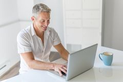 Mature Man Using Laptop On Desk At Home. A mature Man Using Laptop On Desk At Home Royalty Free Stock Image