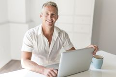 Mature Man Using Laptop On Desk At Home. A mature Man Using Laptop On Desk At Home Stock Photo