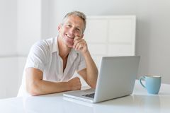 Mature Man Using Laptop On Desk At Home. A mature Man Using Laptop On Desk At Home Royalty Free Stock Photography