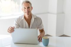 Mature Man Using Laptop On Desk At Home. A mature Man Using Laptop On Desk At Home Stock Images