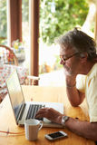 Mature Man Using Laptop In Kitchen. Wearing Glasses Royalty Free Stock Photography