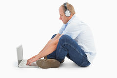 Mature man using laptop listening to music. On white background Royalty Free Stock Image