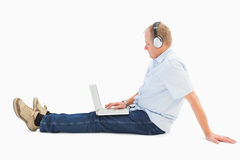 Mature man using laptop listening to music. On white background Stock Photos