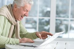 Mature man using laptop. Sitting near window Stock Images