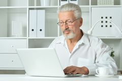Mature man using laptop. Sitting near window Royalty Free Stock Photos
