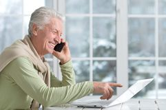 Mature man using laptop. While talking on phone Royalty Free Stock Images