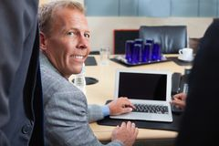 Mature man using laptop in office Royalty Free Stock Images