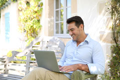Mature man using laptop outdoors on bench Royalty Free Stock Images
