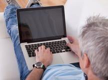 Mature man using laptop Stock Image