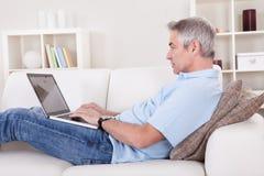 Mature man using laptop Stock Photo