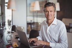 Mature man using laptop in restaurant. Portrait of mature man using laptop in restaurant Royalty Free Stock Images
