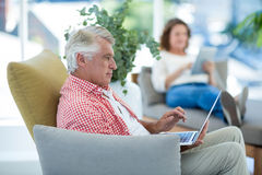 Mature man using laptop at restaurant. Mature man using laptop while woman relaxing in background at restaurant Royalty Free Stock Image