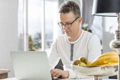 Mature man using laptop at table in house Stock Photos