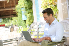 Mature man using laptop on terrace. Mature man on week-end working from home with laptop stock images