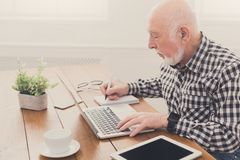 Mature man using laptop and writing in notepad. At home desk. Education, recipe concept Stock Photo