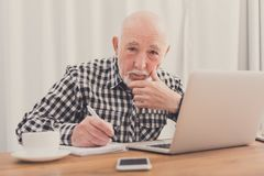 Mature man using laptop and writing in notepad. At home desk. Education, recipe concept Royalty Free Stock Photography